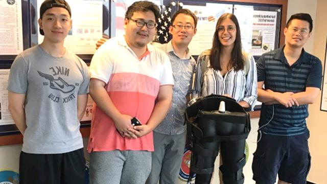 CCNY Mechanical Engineering Professor Hao Su [third from left] with members of his re搜索 team and a model of their exoskeleton.